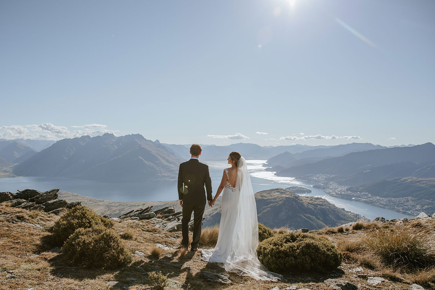 Bride wearing bespoke bridal gown with richly beaded lace over sheer tulle bodice and low back from Auckland wedding dress designer Vinka designs - holding hands facing view
