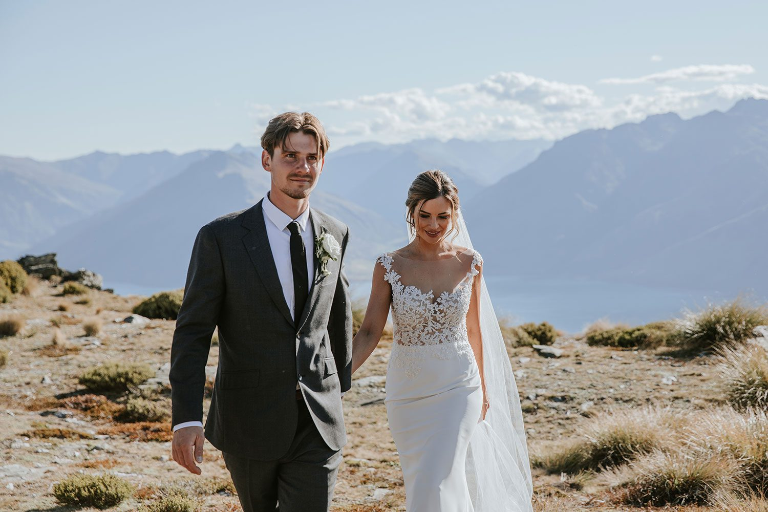 Bride wearing bespoke bridal gown with richly beaded lace over sheer tulle bodice and low back from Auckland wedding dress designer Vinka designs - walking with groom