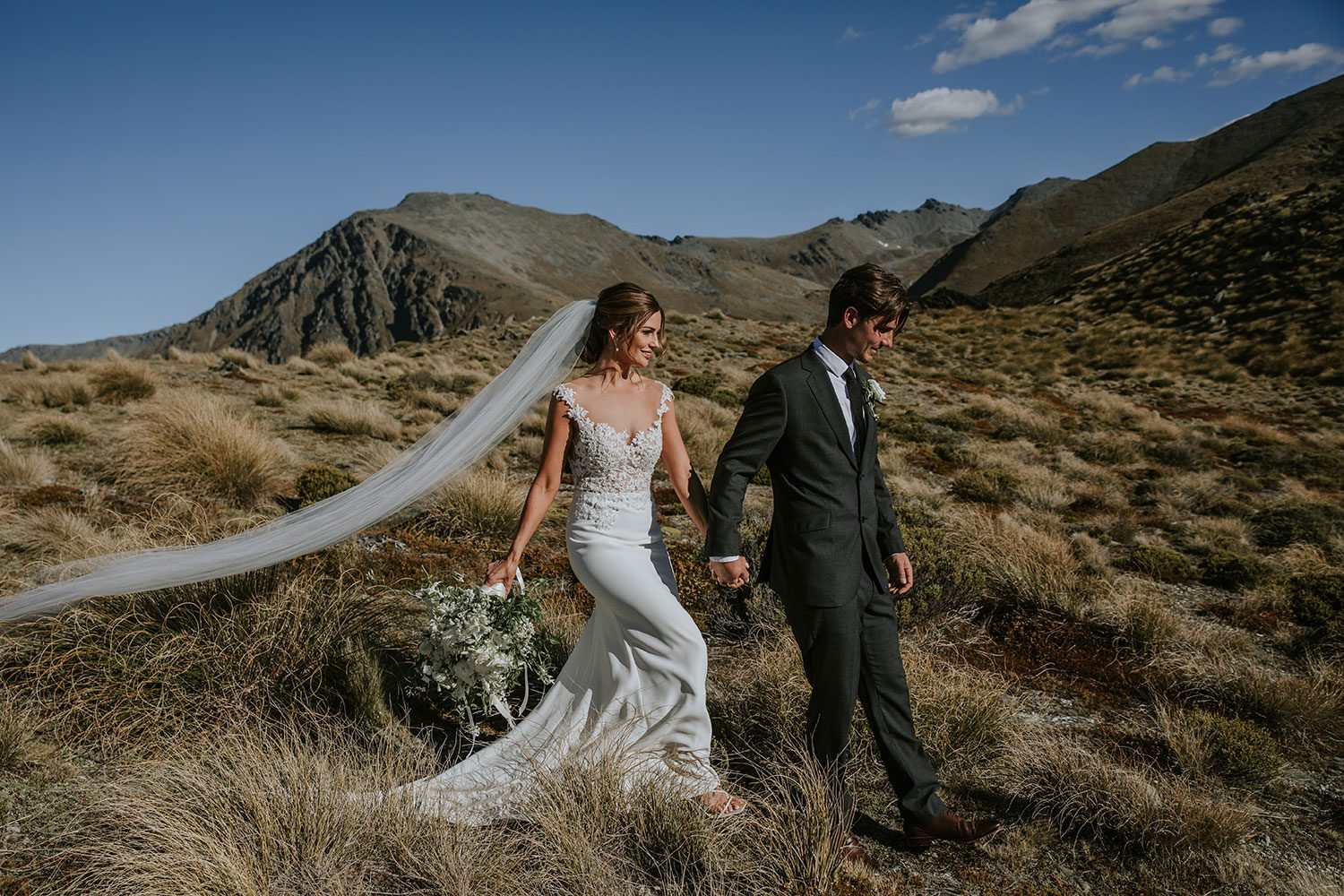 Bride wearing bespoke bridal gown with richly beaded lace over sheer tulle bodice and low back from Auckland wedding dress designer Vinka designs - walking with groom side shot