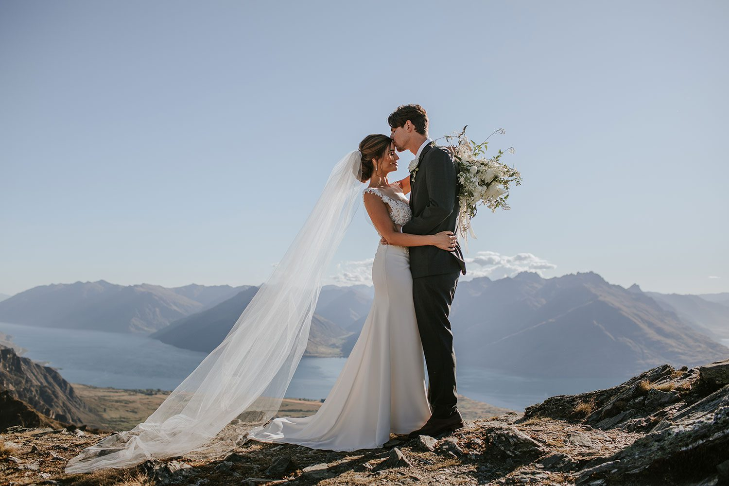 Bride wearing bespoke bridal gown with richly beaded lace over sheer tulle bodice and low back from Auckland wedding dress designer Vinka designs - profile with groom kissing forehead