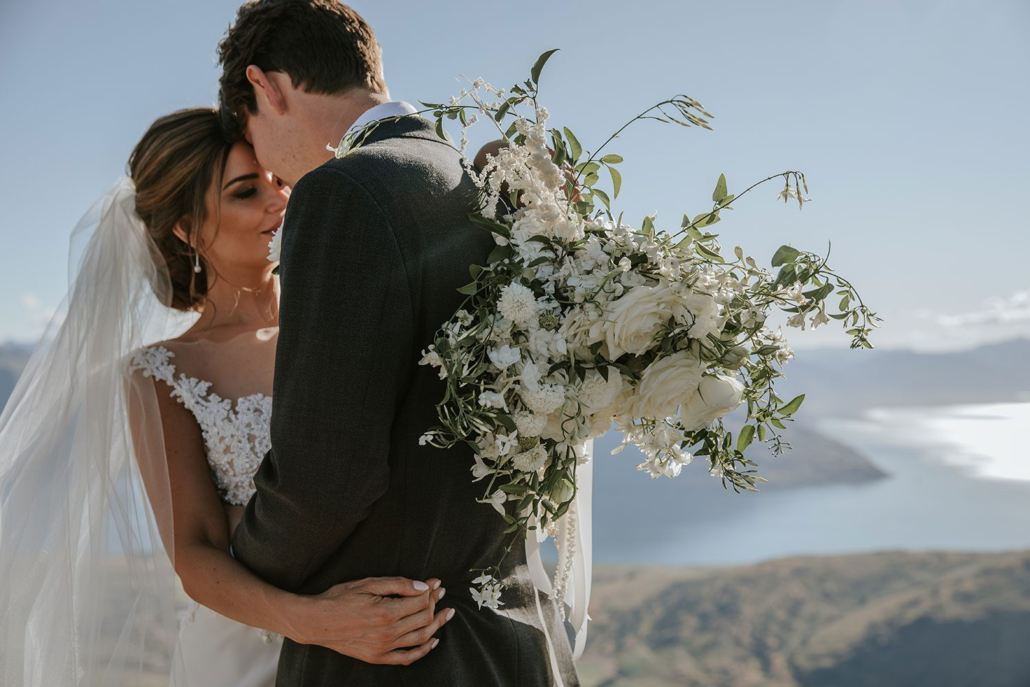 Bride wearing bespoke bridal gown with richly beaded lace over sheer tulle bodice and low back from Auckland wedding dress designer Vinka designs - embrace with groom bouquet