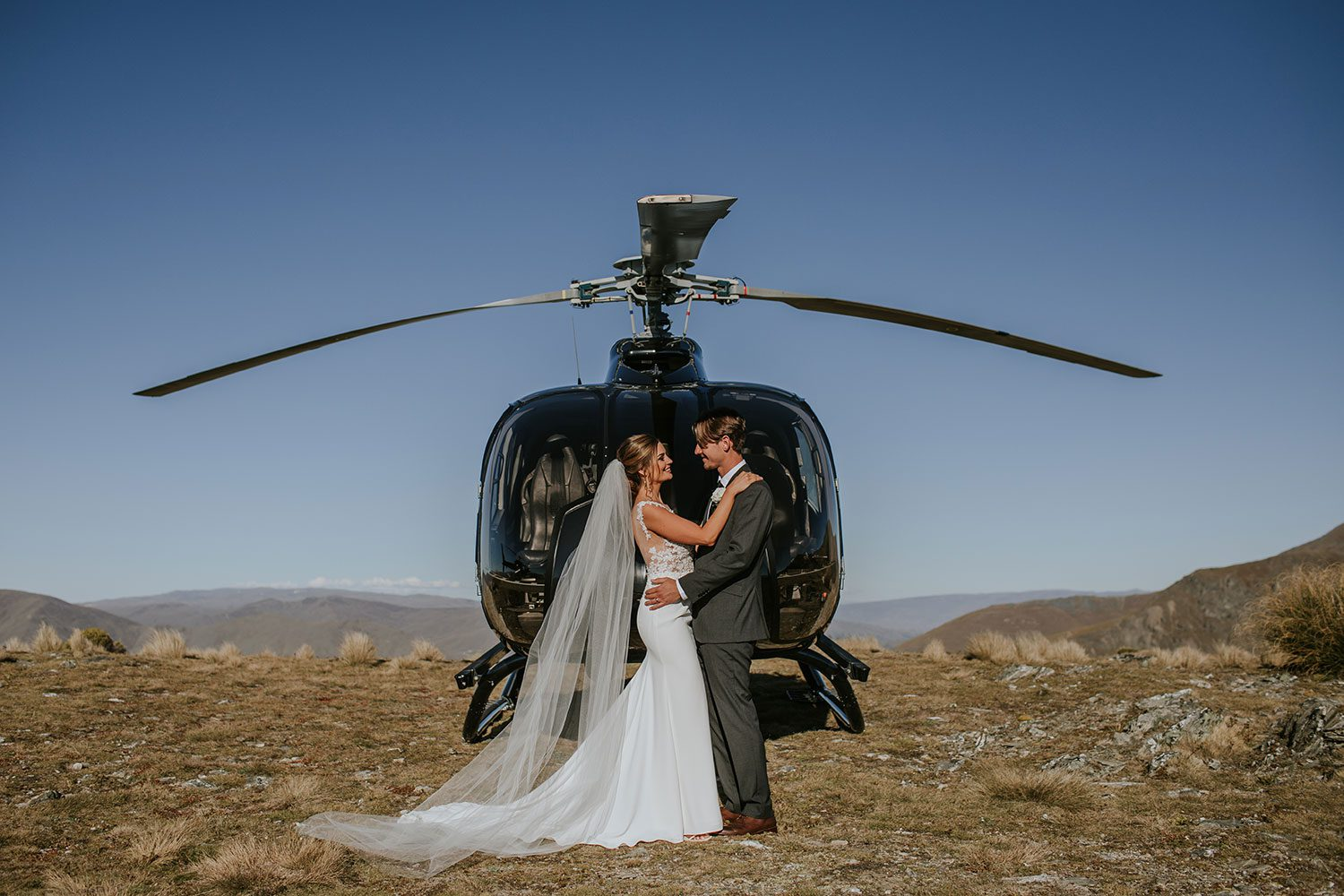 Bride wearing bespoke bridal gown with richly beaded lace over sheer tulle bodice and low back from Auckland wedding dress designer Vinka designs - embrace with groom in front of helicopter