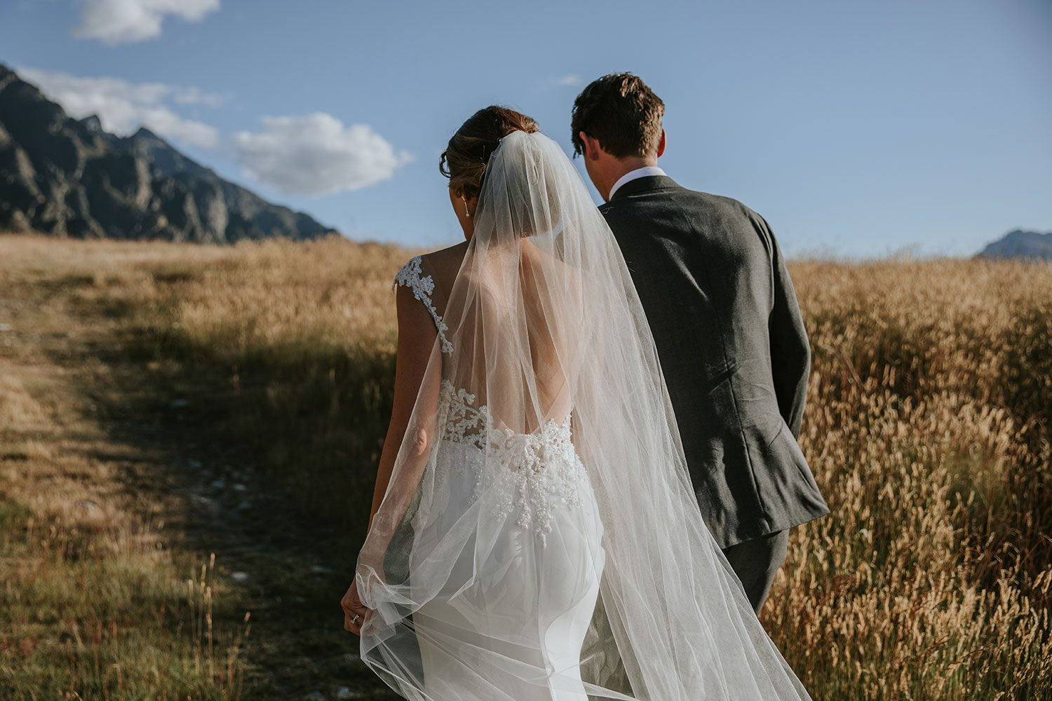 Bride wearing bespoke bridal gown with richly beaded lace over sheer tulle bodice and low back from Auckland wedding dress designer Vinka designs - walking away in field