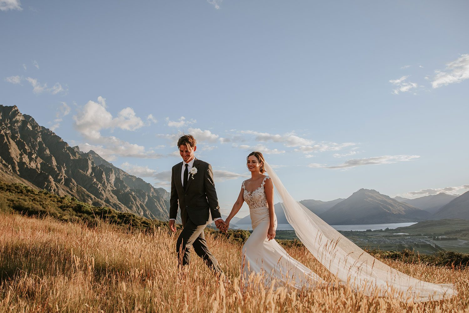 Bride wearing bespoke bridal gown with richly beaded lace over sheer tulle bodice and low back from Auckland wedding dress designer Vinka designs - walking across field with groom