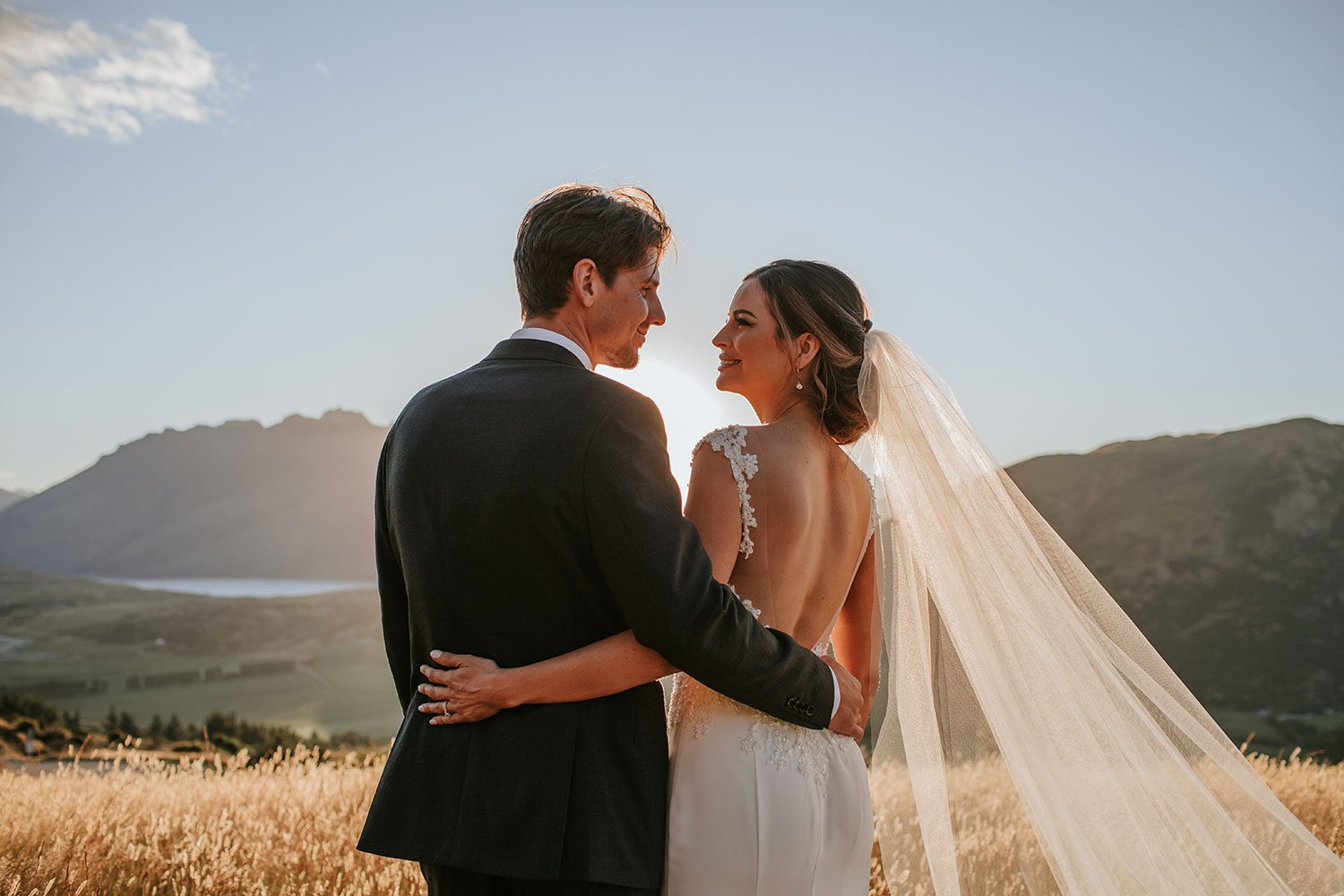 Bride wearing bespoke bridal gown with richly beaded lace over sheer tulle bodice and low back from Auckland wedding dress designer Vinka designs - with groom back embrace in field