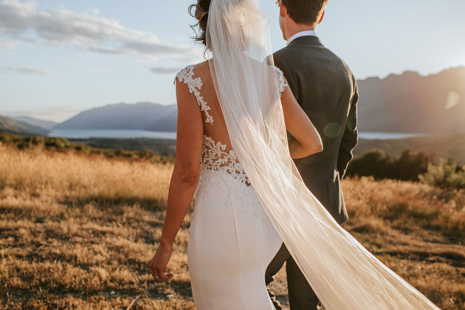 Bride wearing bespoke bridal gown with richly beaded lace over sheer tulle bodice and low back from Auckland wedding dress designer Vinka designs - with groom in field close up of back