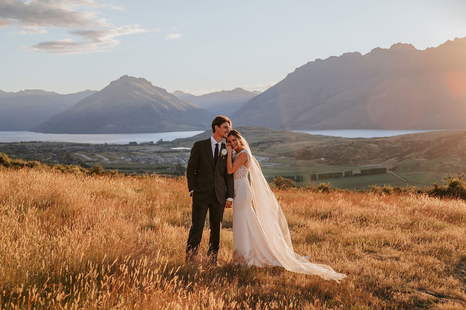 Bride wearing bespoke bridal gown with richly beaded lace over sheer tulle bodice and low back from Auckland wedding dress designer Vinka designs - in field leaning on groom