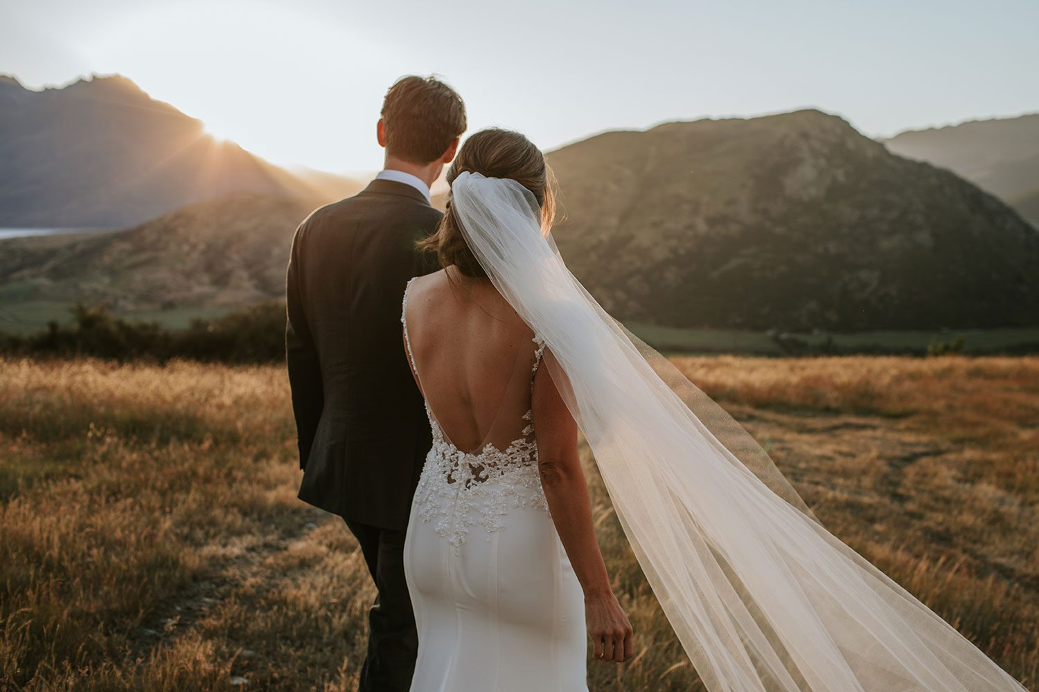 Bride wearing bespoke bridal gown with richly beaded lace over sheer tulle bodice and low back from Auckland wedding dress designer Vinka designs - in field close up of back veil in wind