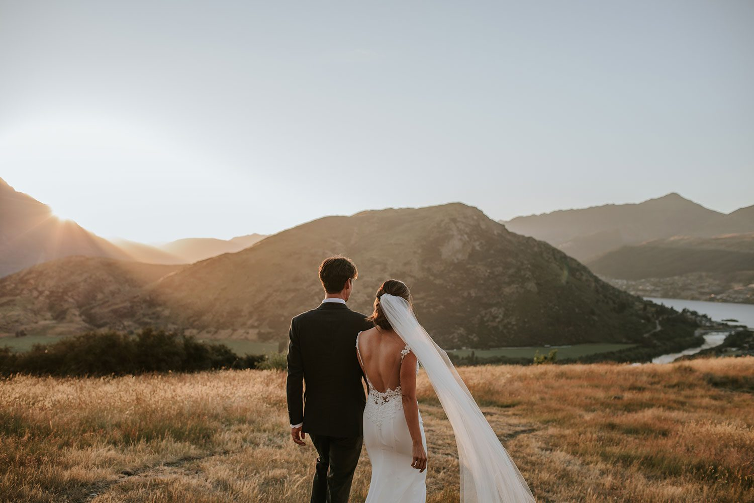 Bride wearing bespoke bridal gown with richly beaded lace over sheer tulle bodice and low back from Auckland wedding dress designer Vinka designs - in field with groom sun setting