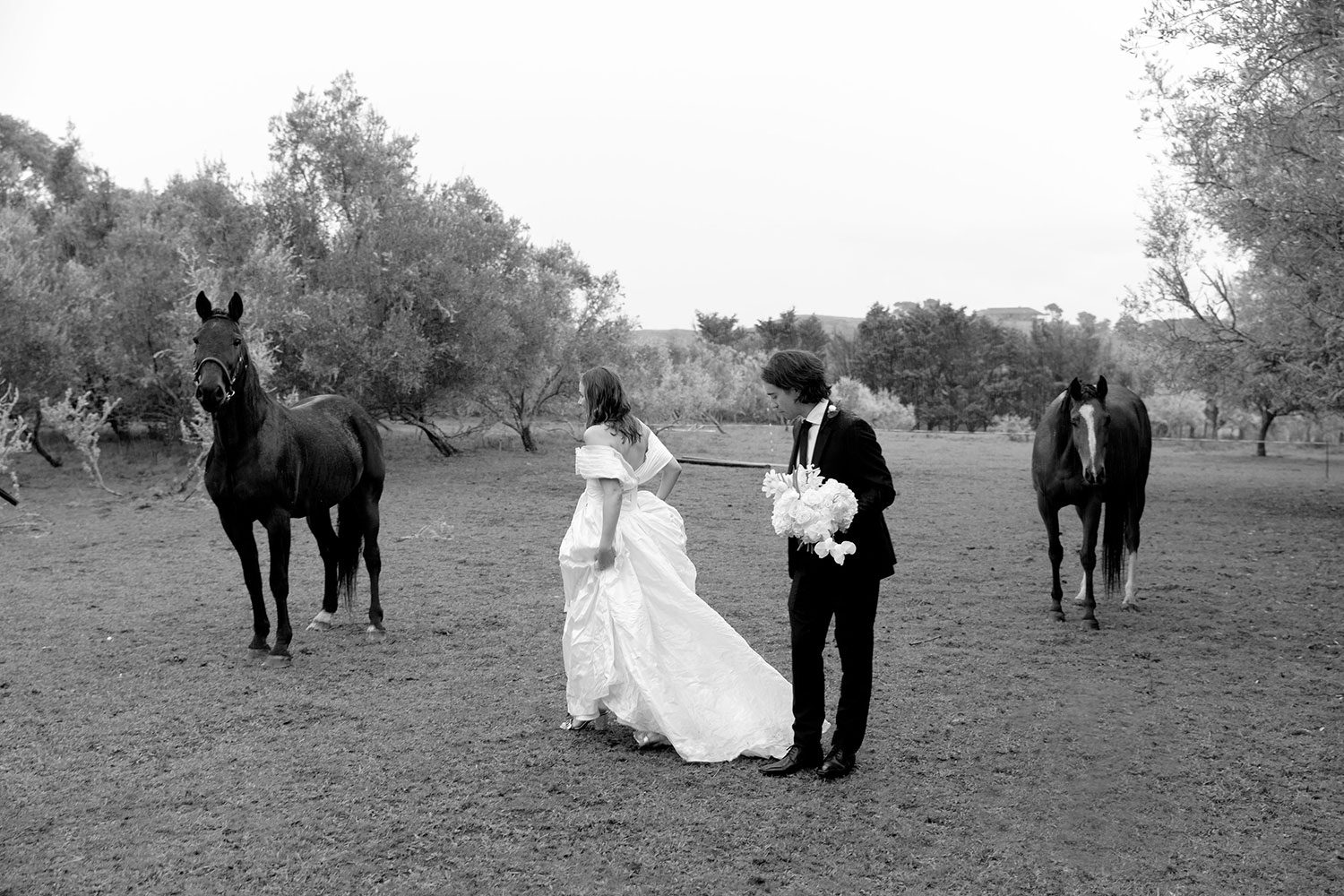 Bride wearing bespoke off shoulder bodice made with silk dupion and long train by NZ wedding dress maker Vinka Designs - black and white with groom and horses in field