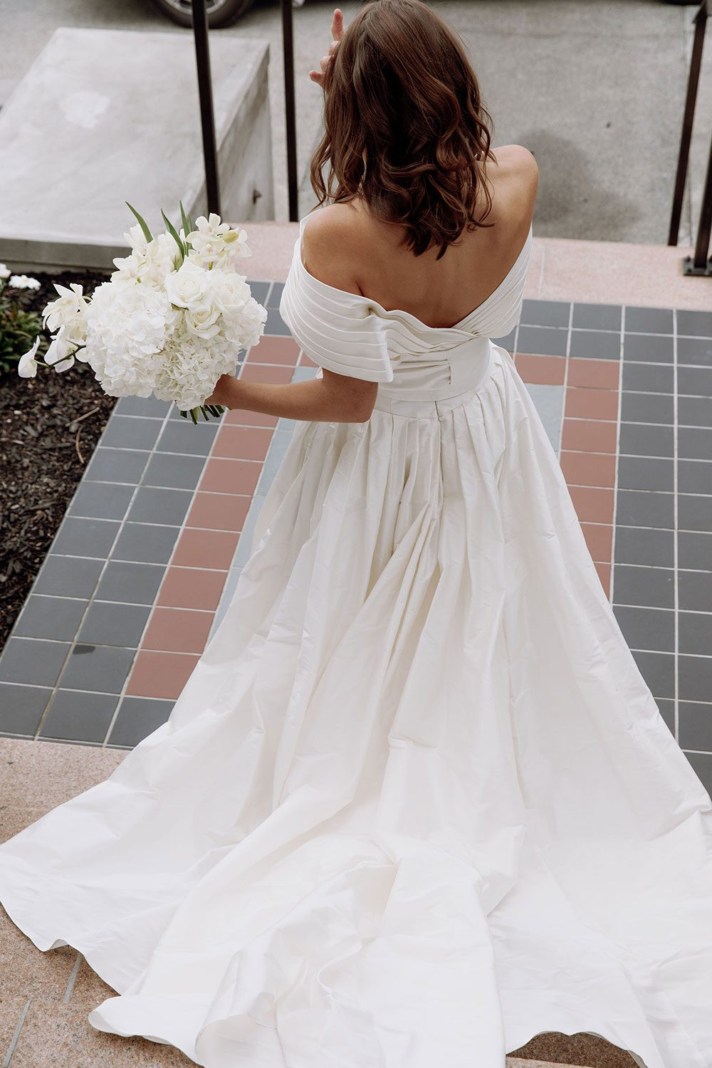 Bride wearing bespoke off shoulder bodice made with silk dupion and long train by NZ wedding dress maker Vinka Designs - back of dress and bouquet