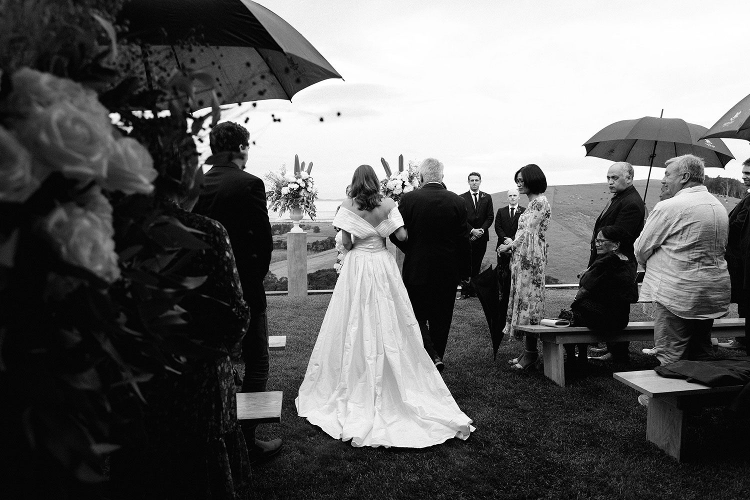 Bride wearing bespoke off shoulder bodice made with silk dupion and long train by NZ wedding dress maker Vinka Designs - black and white walking down aisle