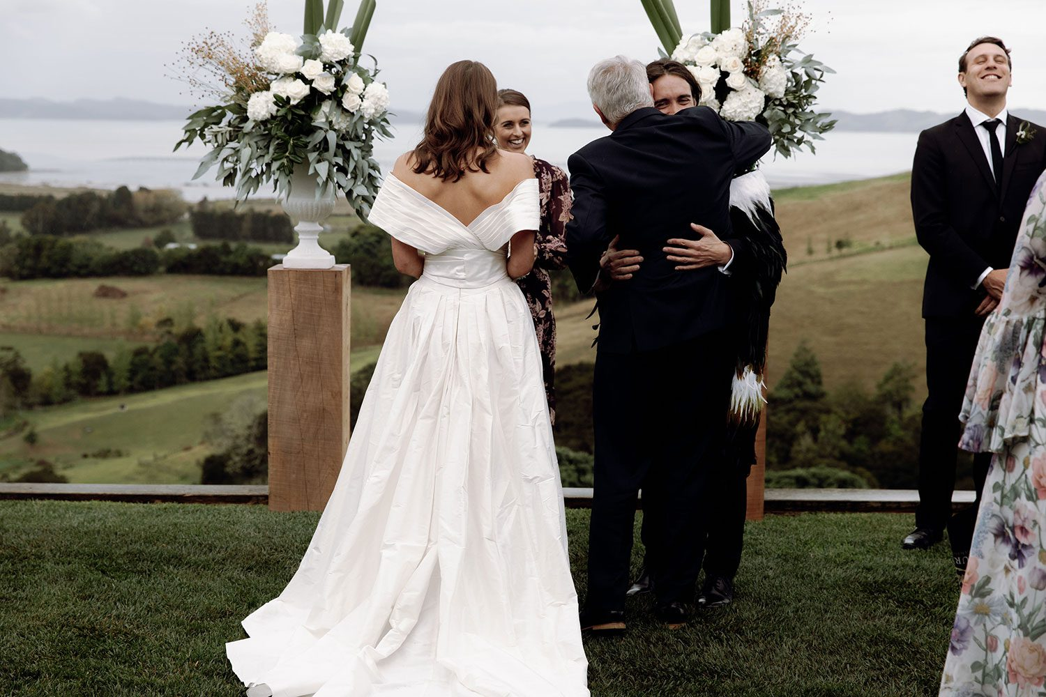Bride wearing bespoke off shoulder bodice made with silk dupion and long train by NZ wedding dress maker Vinka Designs - giving away