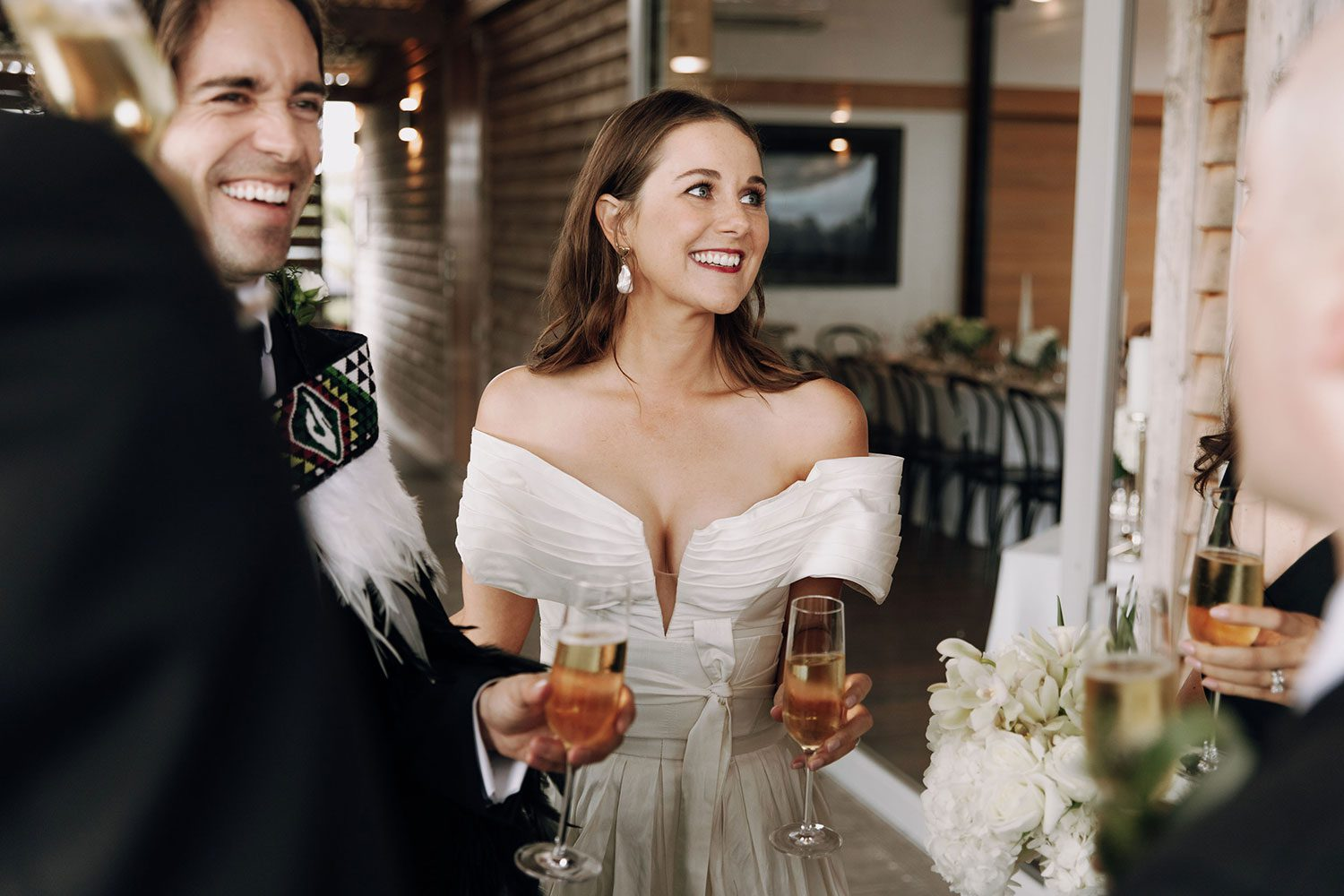 Bride wearing bespoke off shoulder bodice made with silk dupion and long train by NZ wedding dress maker Vinka Designs - laughing with groom