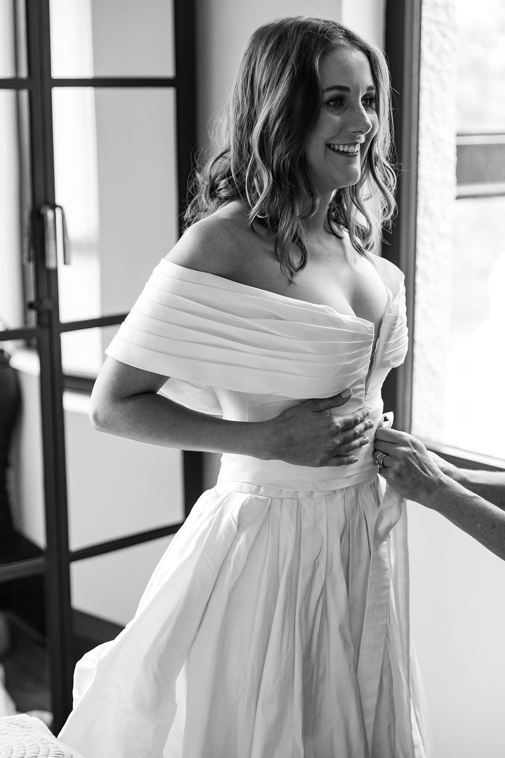 Bride wearing bespoke off shoulder bodice made with silk dupion and long train by NZ wedding dress maker Vinka Designs - black and white getting ready