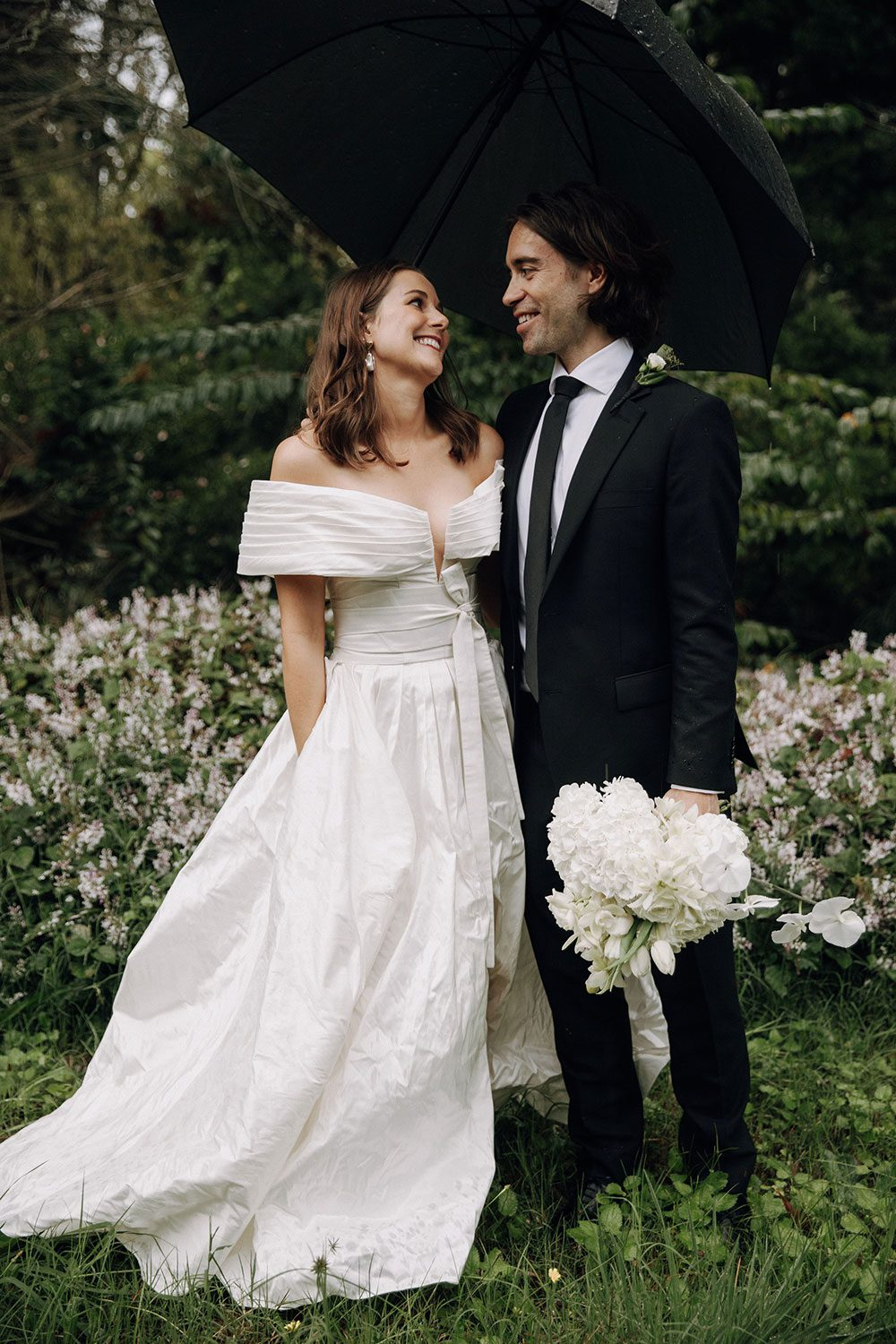 Bride wearing bespoke off shoulder bodice made with silk dupion and long train by NZ wedding dress maker Vinka Designs - laughing with groom under umbrella outside