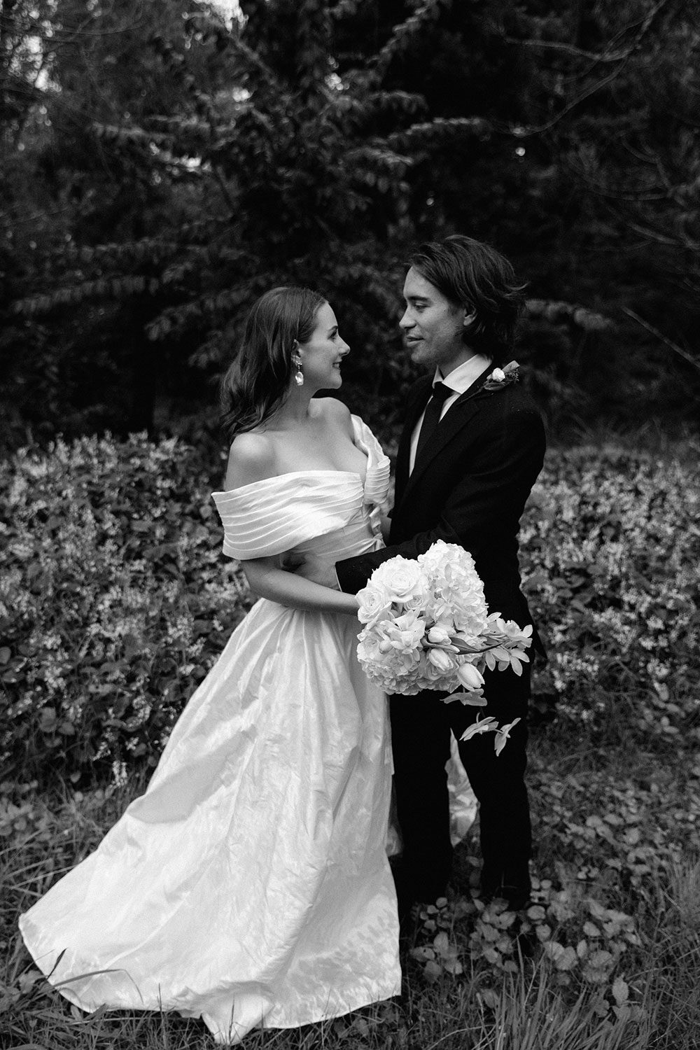 Bride wearing bespoke off shoulder bodice made with silk dupion and long train by NZ wedding dress maker Vinka Designs - black and white kissing groom under umbrella