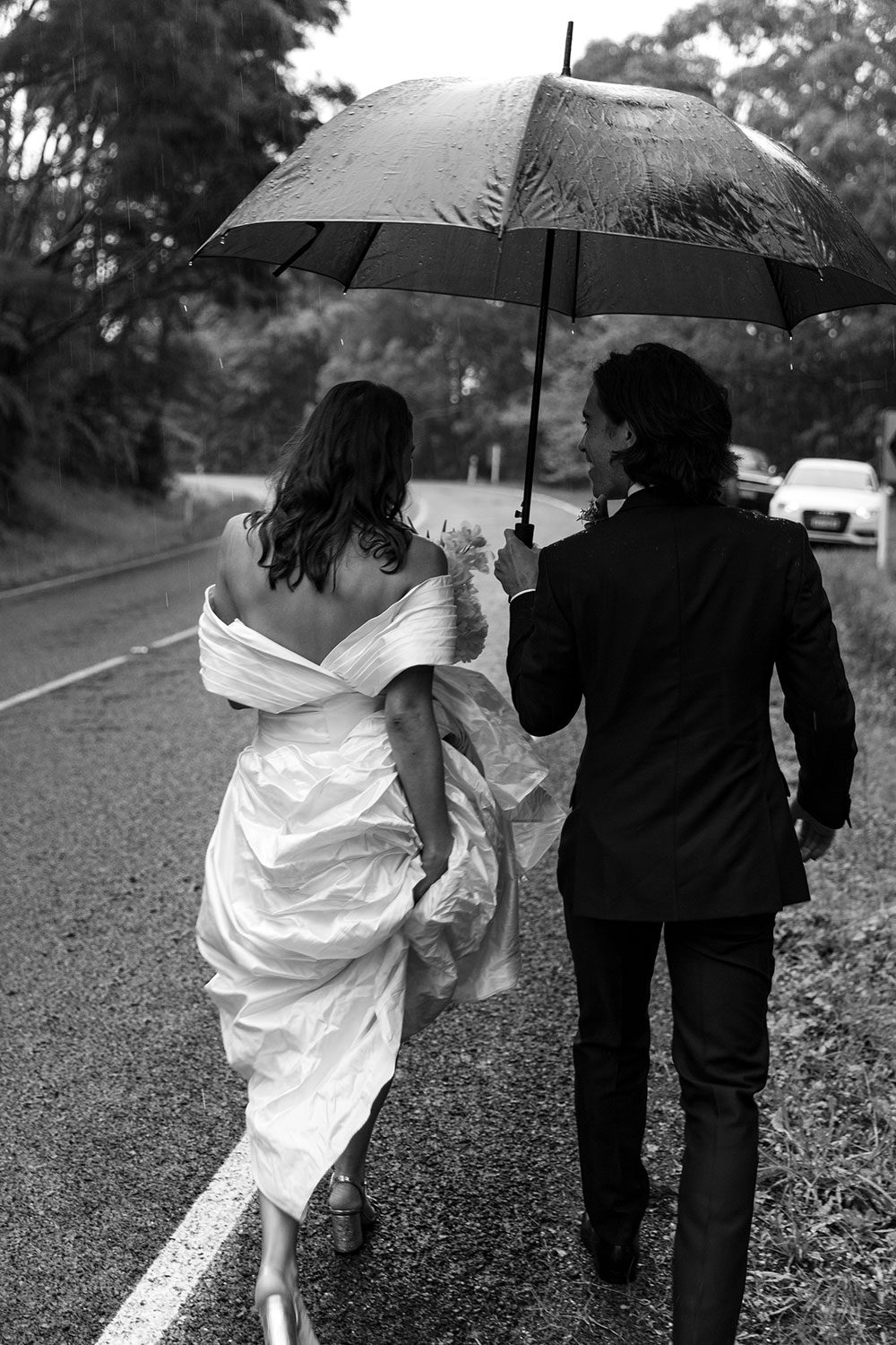 Bride wearing bespoke off shoulder bodice made with silk dupion and long train by NZ wedding dress maker Vinka Designs - black and white walking with groom under umbrella