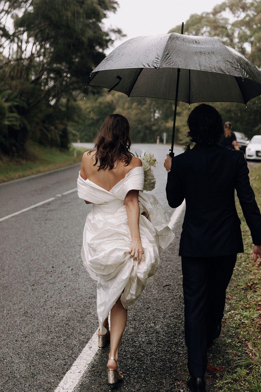 Bride wearing bespoke design by NZ wedding dress maker Vinka Designs - walking with groom under umbrella
