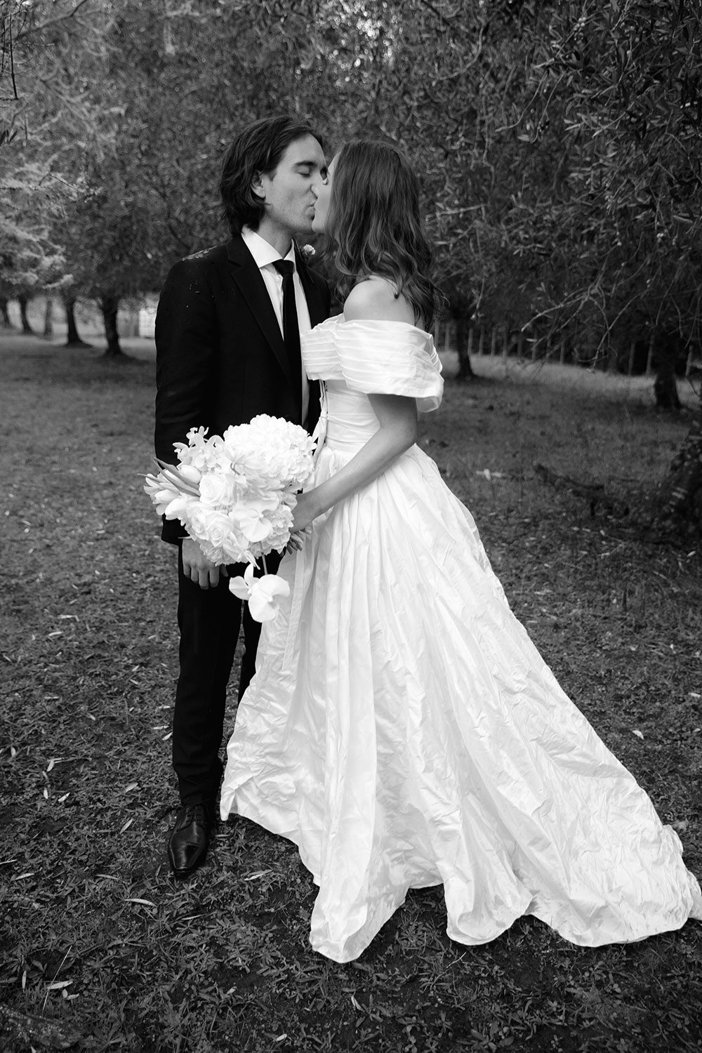 Bride wearing bespoke off shoulder bodice made with silk dupion and long train by NZ wedding dress maker Vinka Designs - black and white kissing groom outside