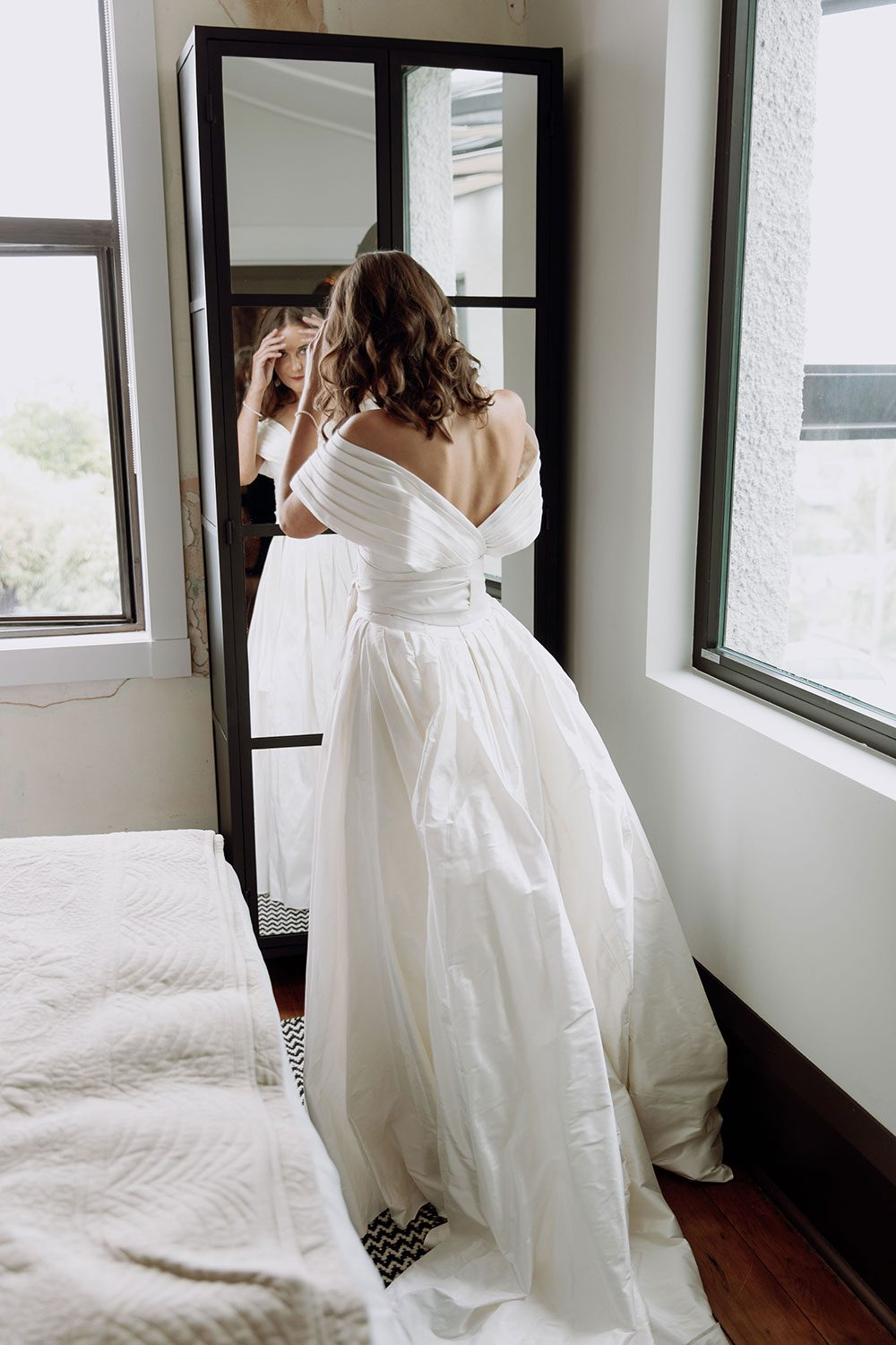 Bride wearing bespoke off shoulder bodice made with silk dupion and long train by NZ wedding dress maker Vinka Designs - at mirror