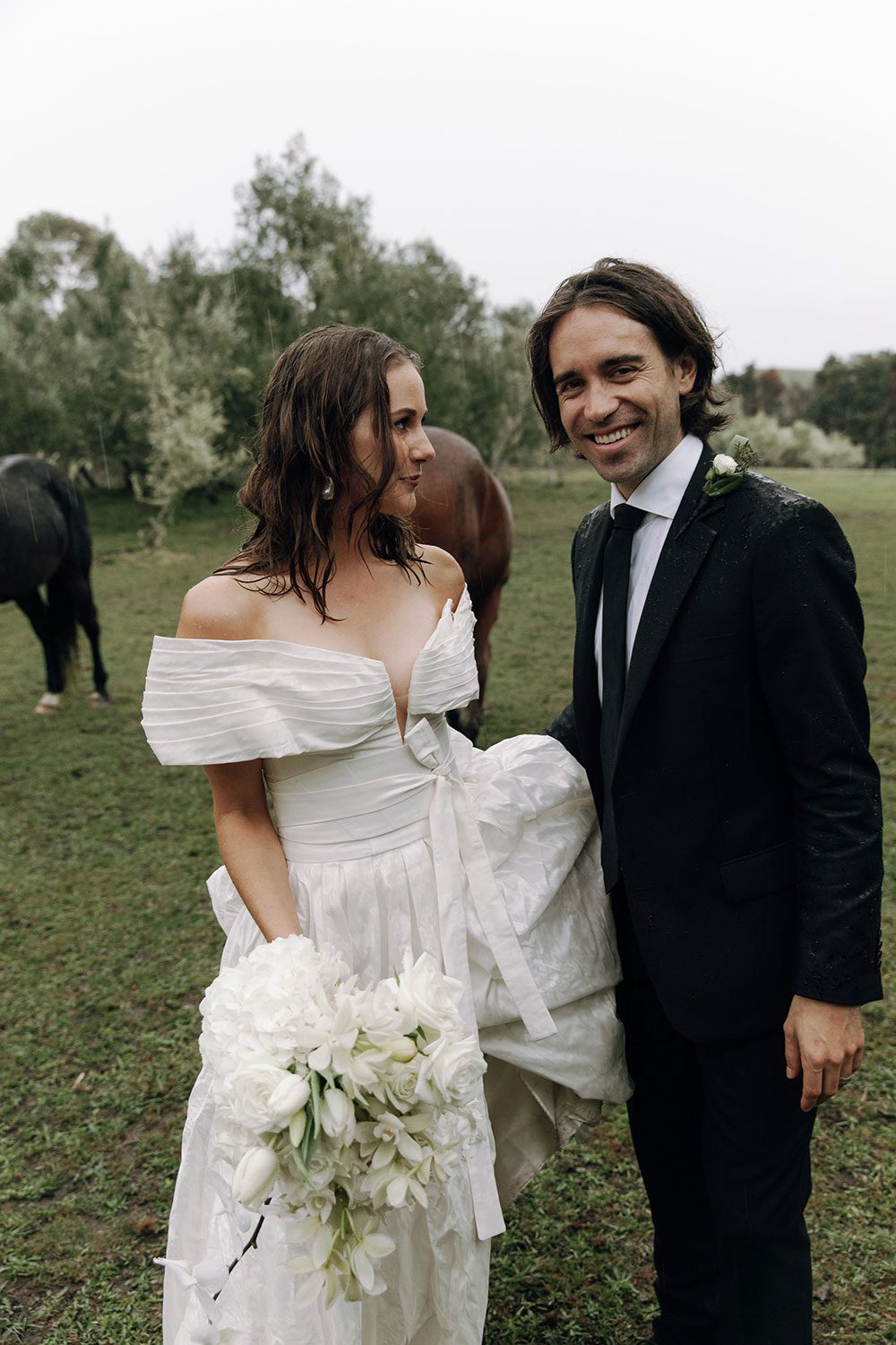 Bride wearing bespoke off shoulder bodice made with silk dupion and long train by NZ wedding dress maker Vinka Designs - with groom in field with horses