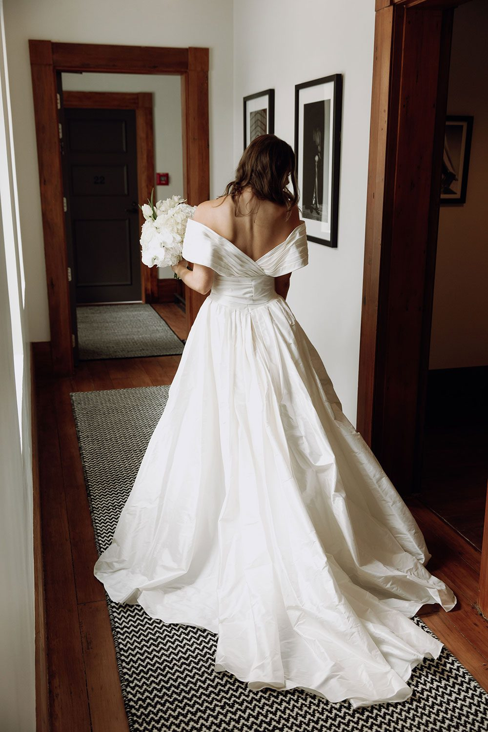 Bride wearing bespoke off shoulder bodice made with silk dupion and long train by NZ wedding dress maker Vinka Designs - back view in doorway
