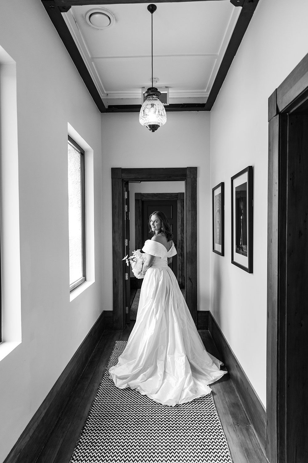 Bride wearing bespoke off shoulder bodice made with silk dupion and long train design by NZ wedding dress maker Vinka Designs - black and white back view in doorway