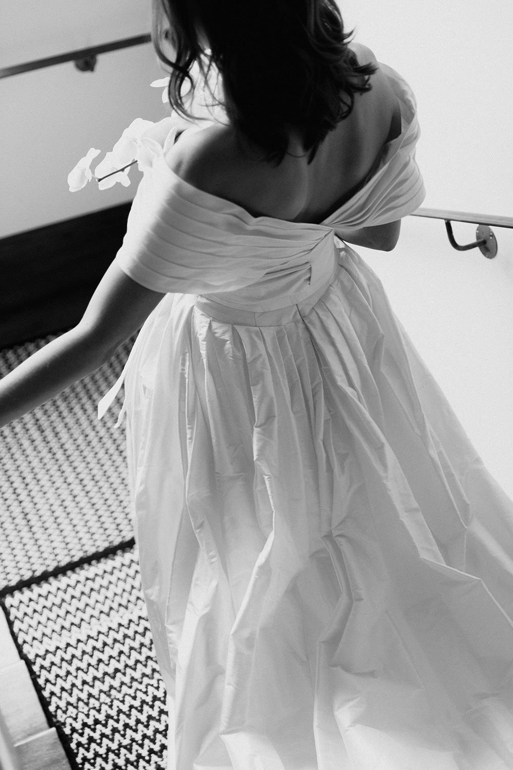 Bride wearing bespoke off shoulder bodice made with silk dupion and long train by NZ wedding dress maker Vinka Designs - black and white back view on stairs