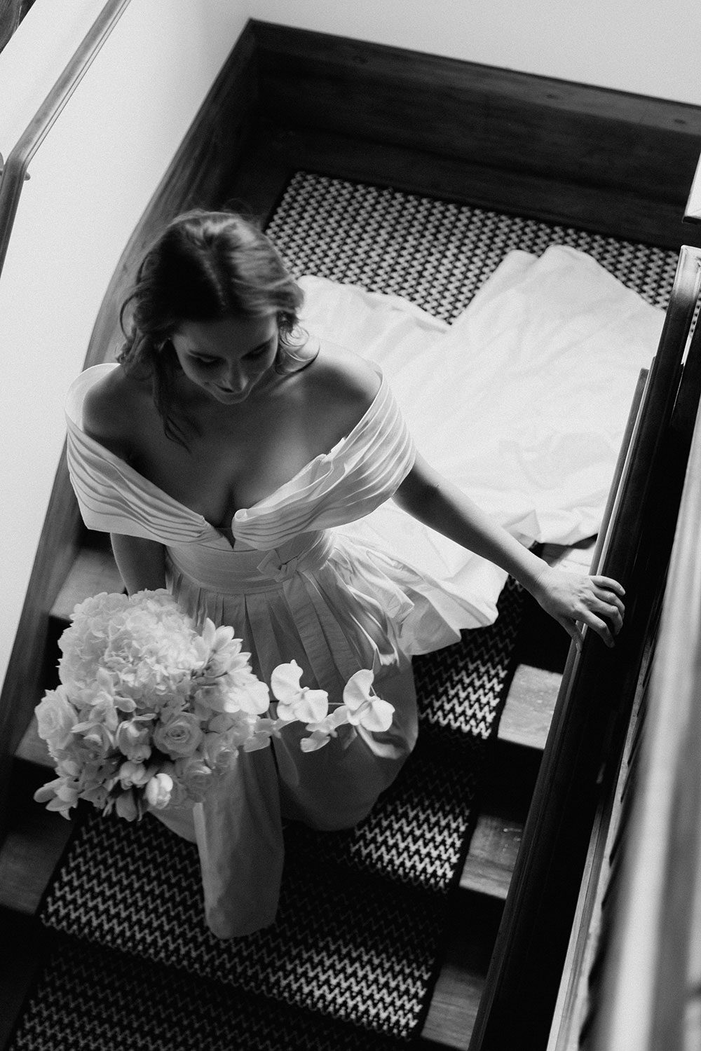 Bride wearing bespoke off shoulder bodice made with silk dupion and long train by NZ wedding dress maker Vinka Designs - black and white overhead on stairs
