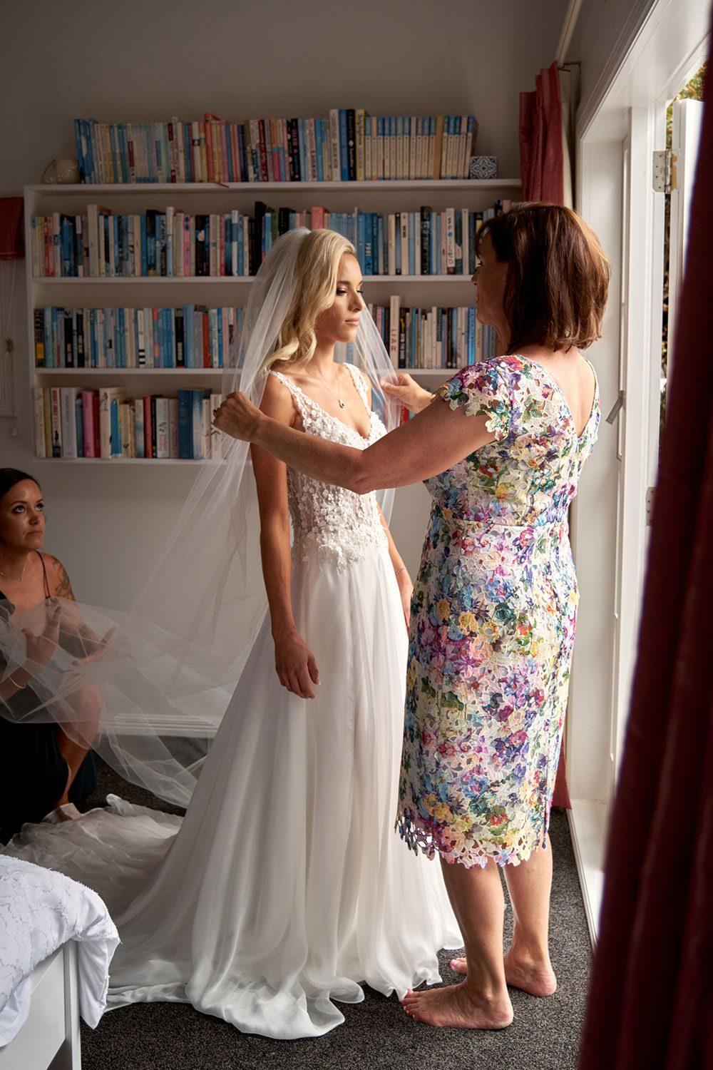 Bride wearing bespoke gown made of silk chiffon with delicate flower lace bodice by Vinka bridal designer Auckland - getting ready in window