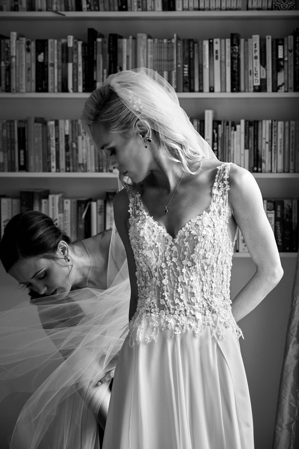 Bride wearing bespoke gown made of silk chiffon with delicate flower lace bodice by Vinka bridal designer Auckland - black and white looking down at veil