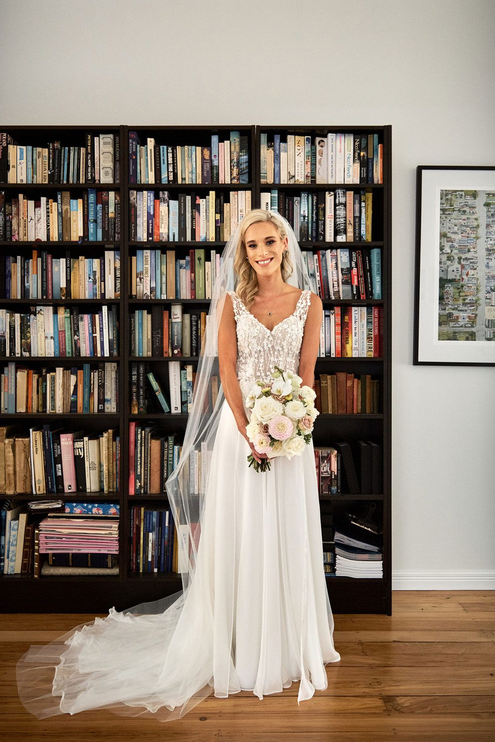 Bride wearing bespoke gown made of silk chiffon with delicate flower lace bodice by Vinka bridal designer Auckland - in front of bookshelf
