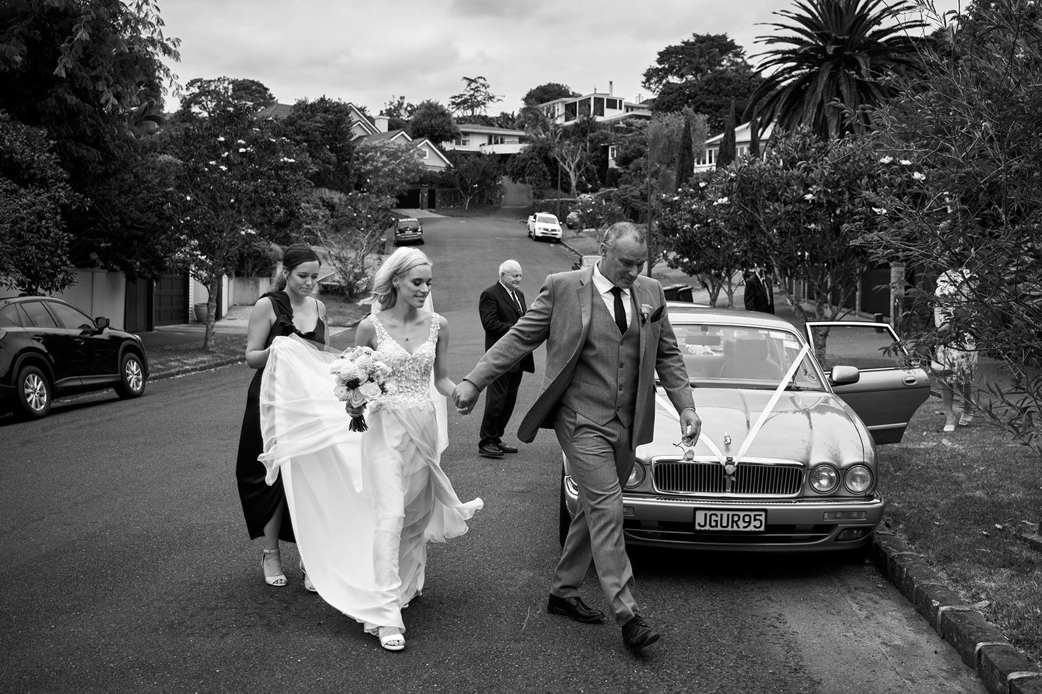 Bride wearing bespoke gown made of silk chiffon with delicate flower lace bodice by Vinka bridal designer Auckland - black and white in front of car