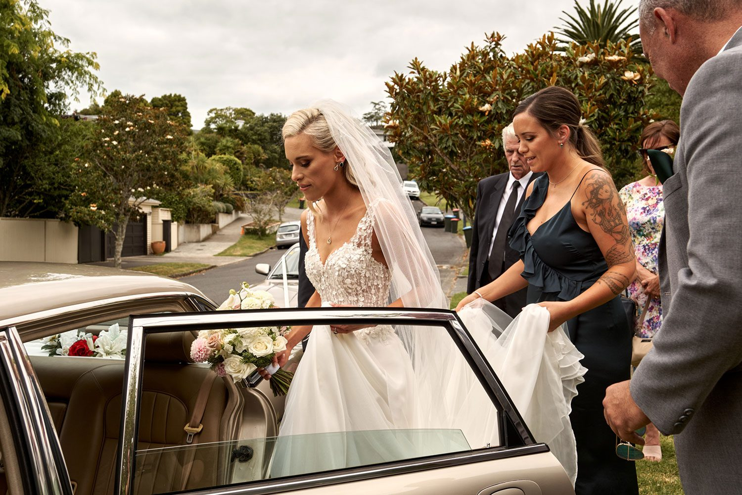 Bride wearing bespoke gown made of silk chiffon with delicate flower lace bodice by Vinka bridal designer Auckland - getting into car