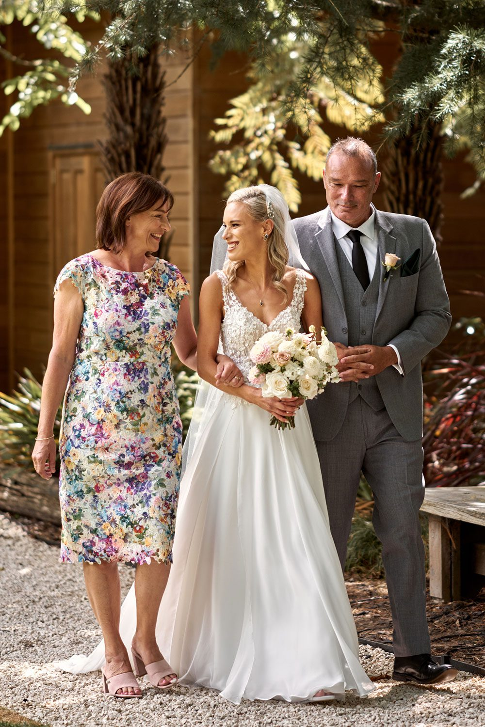 Bride wearing bespoke gown made of silk chiffon with delicate flower lace bodice by Vinka bridal designer Auckland - walking with family