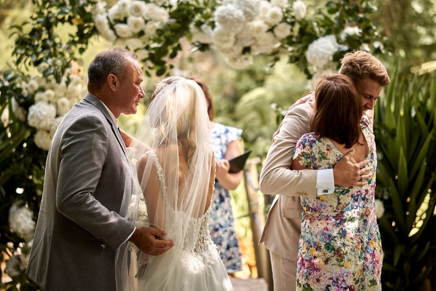 Bride wearing bespoke gown made of silk chiffon with delicate flower lace bodice by Vinka bridal designer Auckland - at alter groom hugging mother
