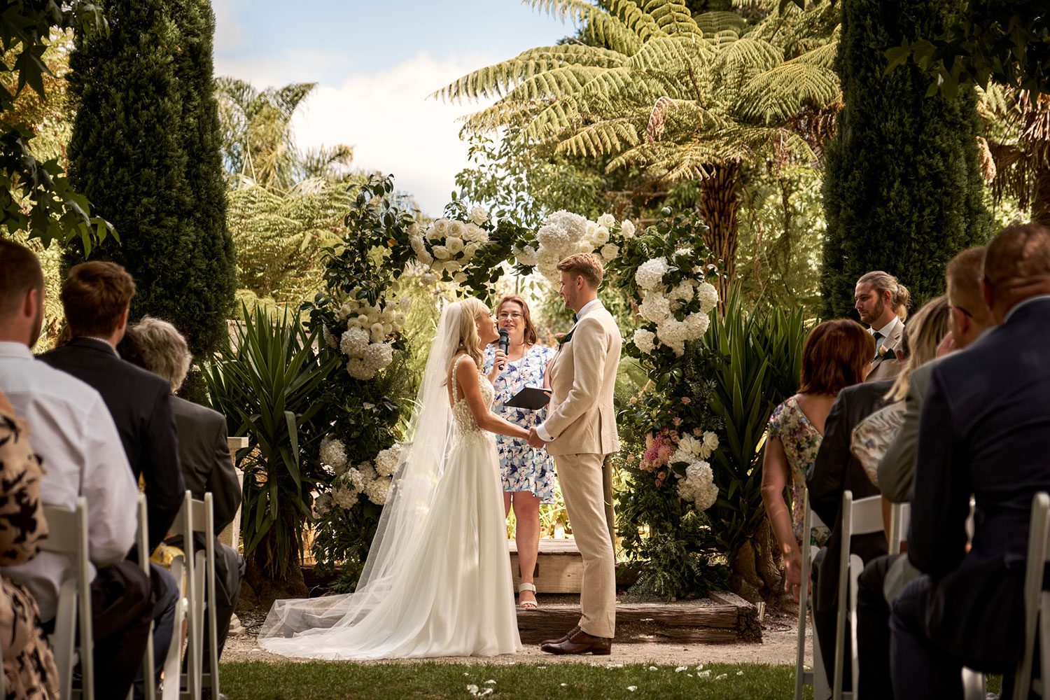 Bride wearing bespoke gown made of silk chiffon with delicate flower lace bodice by Vinka bridal designer Auckland - at alter saying vows with guests seated
