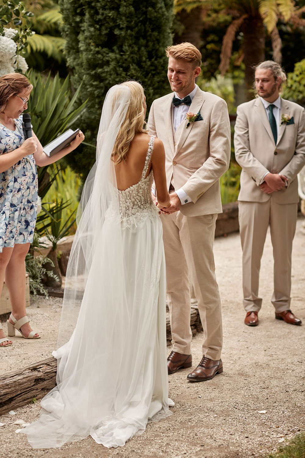 Bride wearing bespoke gown made of silk chiffon with delicate flower lace bodice by Vinka bridal designer Auckland - at alter with groom