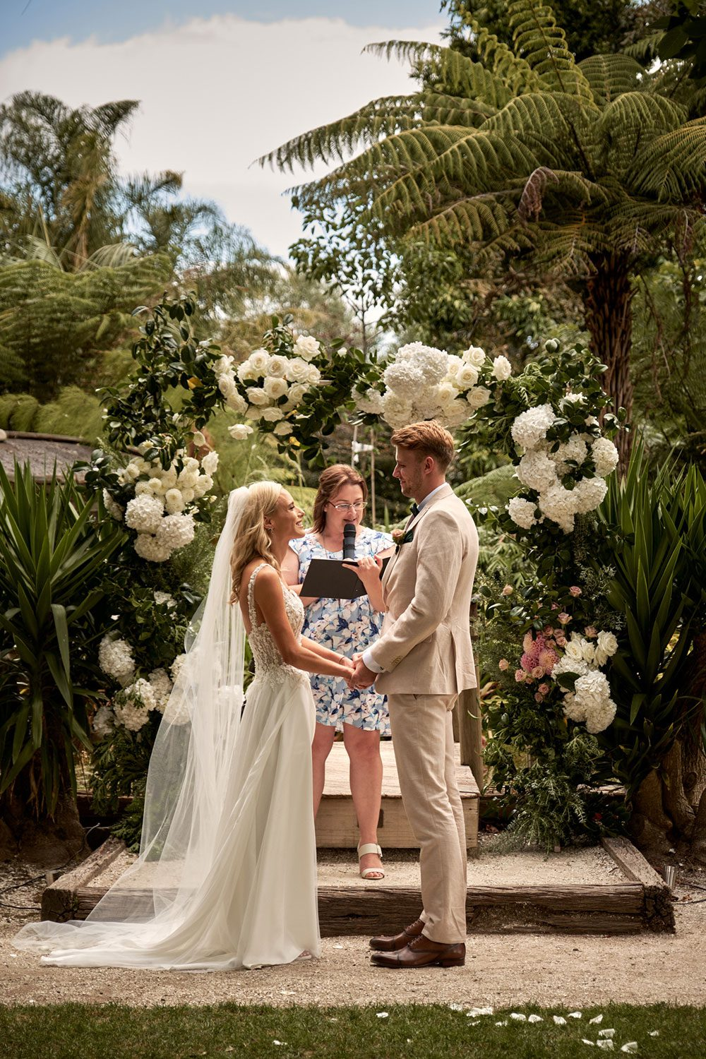 Bride wearing bespoke gown made of silk chiffon with delicate flower lace bodice by Vinka bridal designer Auckland - with groom and celebrant at alter