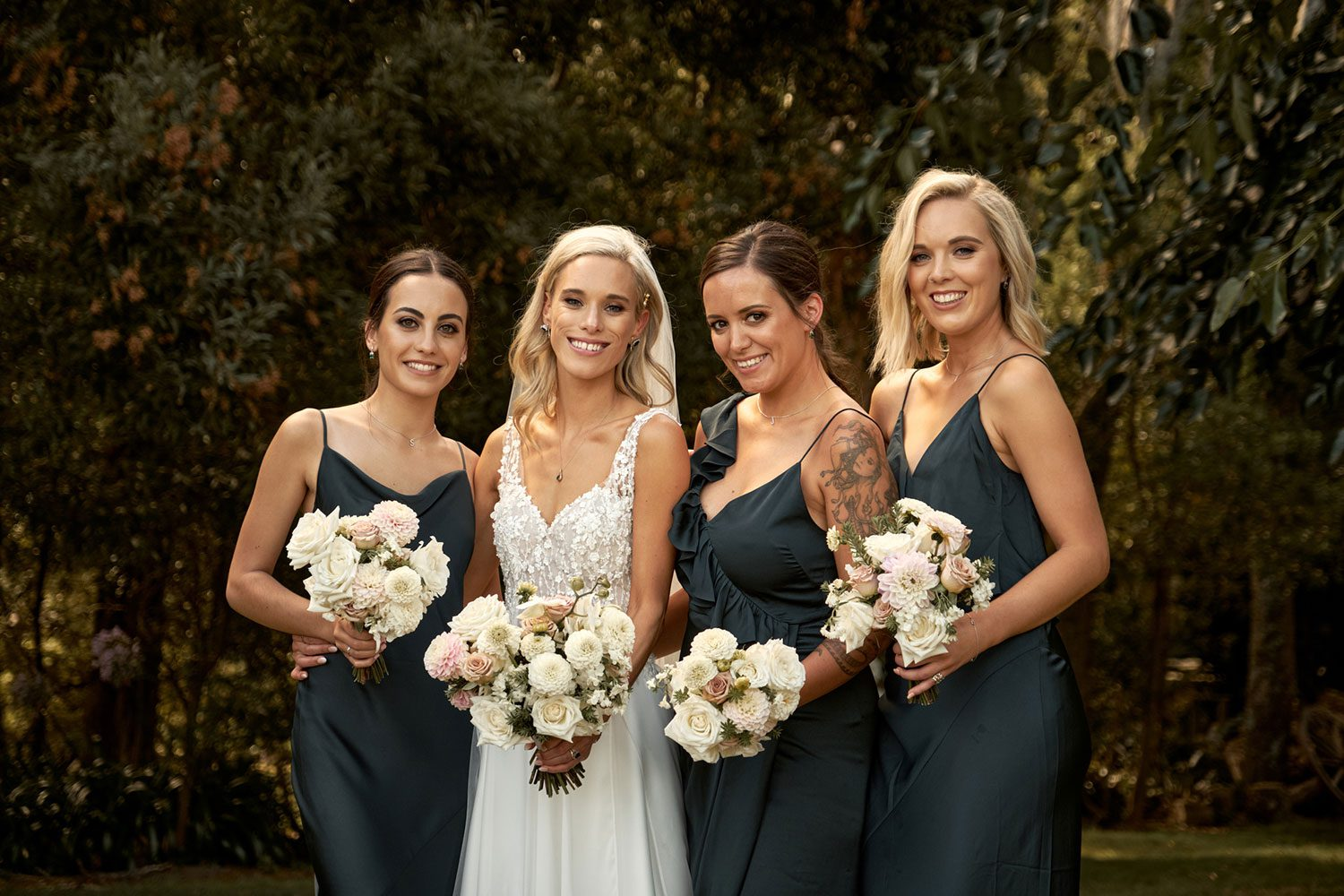 Bride wearing bespoke gown made of silk chiffon with delicate flower lace bodice by Vinka bridal designer Auckland - with bridesmaids and bouquets