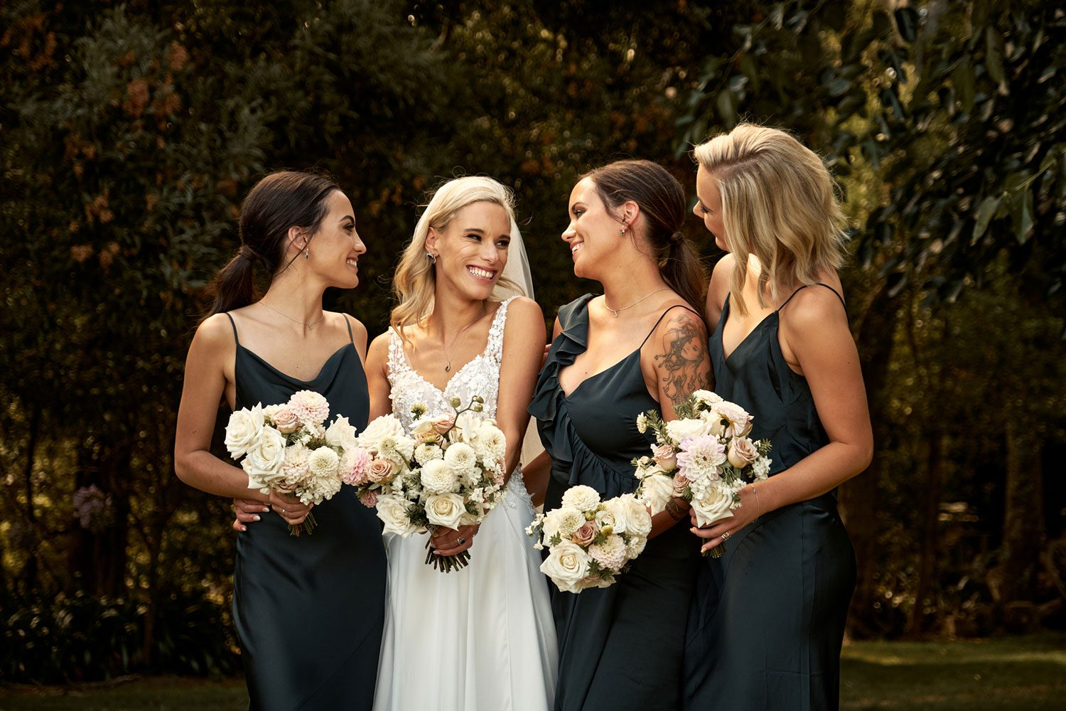 Bride wearing bespoke gown made of silk chiffon with delicate flower lace bodice by Vinka bridal designer Auckland - with bridesmaids and bouquets looking at each other