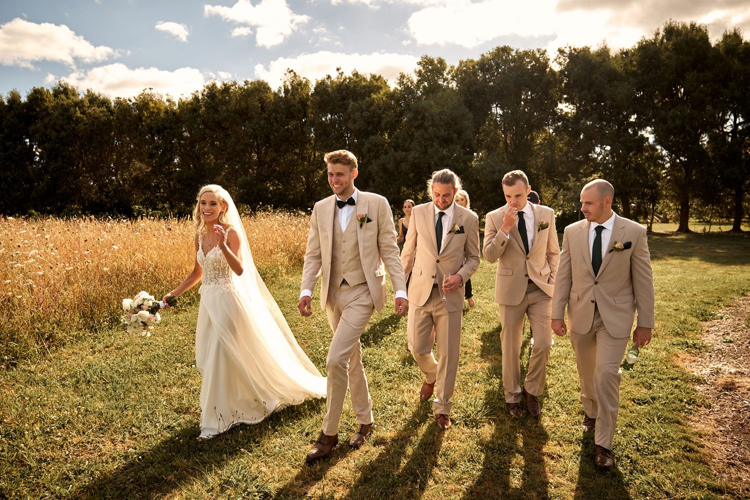 Bride wearing bespoke gown made of silk chiffon with delicate flower lace bodice by Vinka bridal designer Auckland - with groom and groomsmen in field