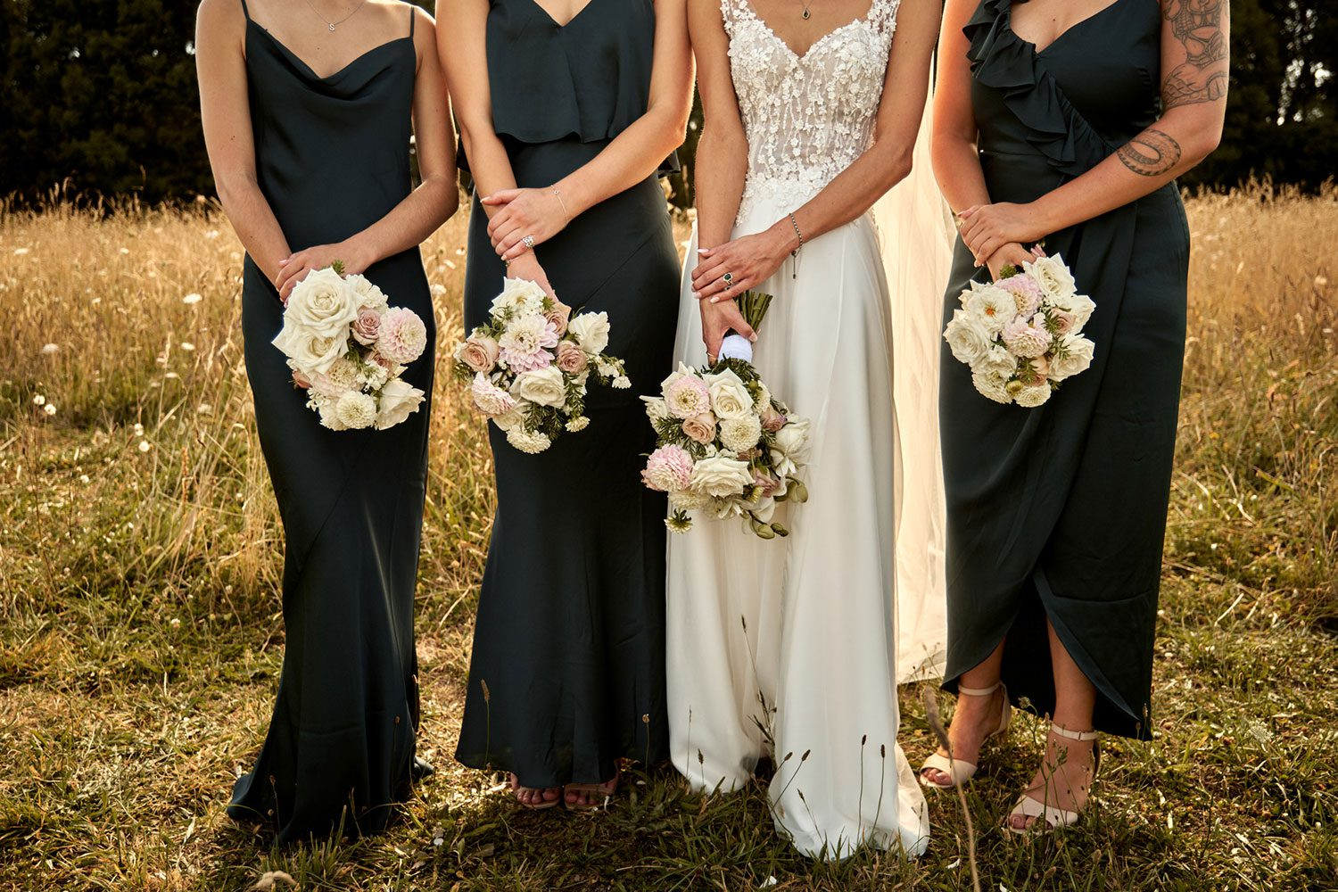 Bride wearing bespoke gown made of silk chiffon with delicate flower lace bodice by Vinka bridal designer Auckland - dress and bouquet shot in field with bridesmaids