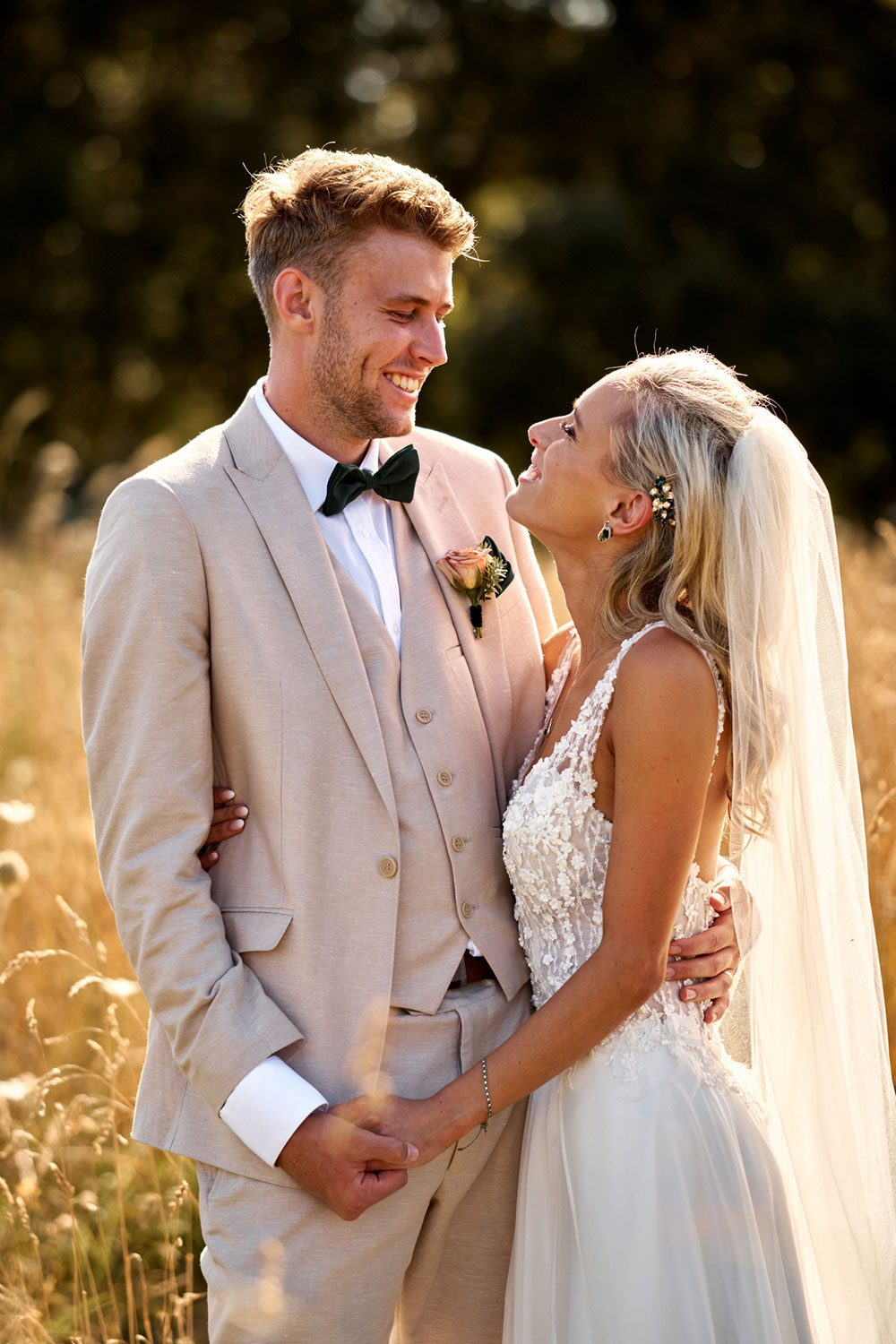 Bride wearing bespoke gown made of silk chiffon with delicate flower lace bodice by Vinka bridal designer Auckland - with groom looking at each other in field