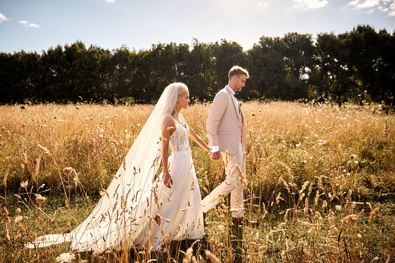 Bride wearing bespoke gown made of silk chiffon with delicate flower lace bodice by Vinka bridal designer Auckland - in profile with groom walking in field