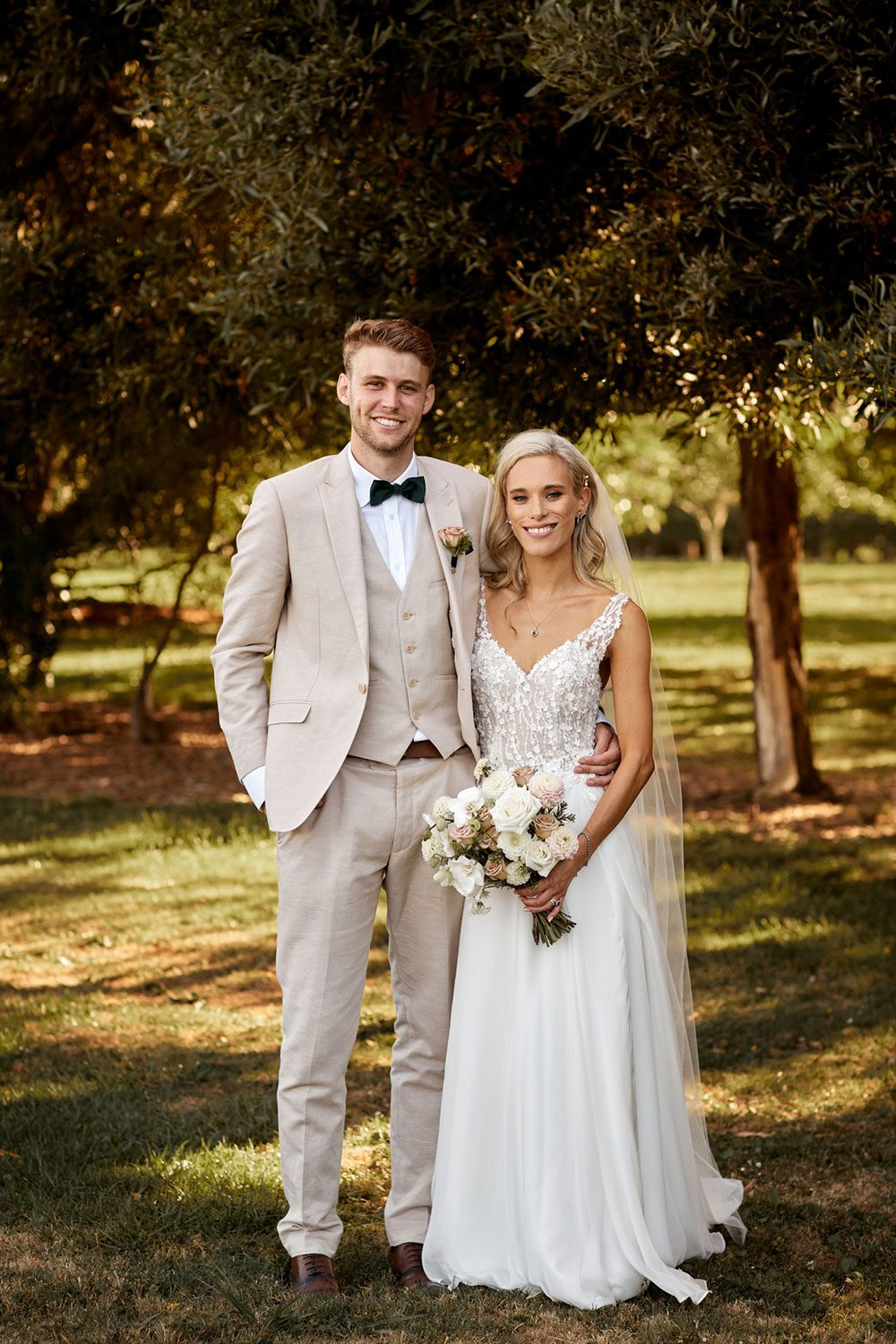 Bride wearing bespoke gown made of silk chiffon with delicate flower lace bodice by Vinka bridal designer Auckland - full length with groom outside