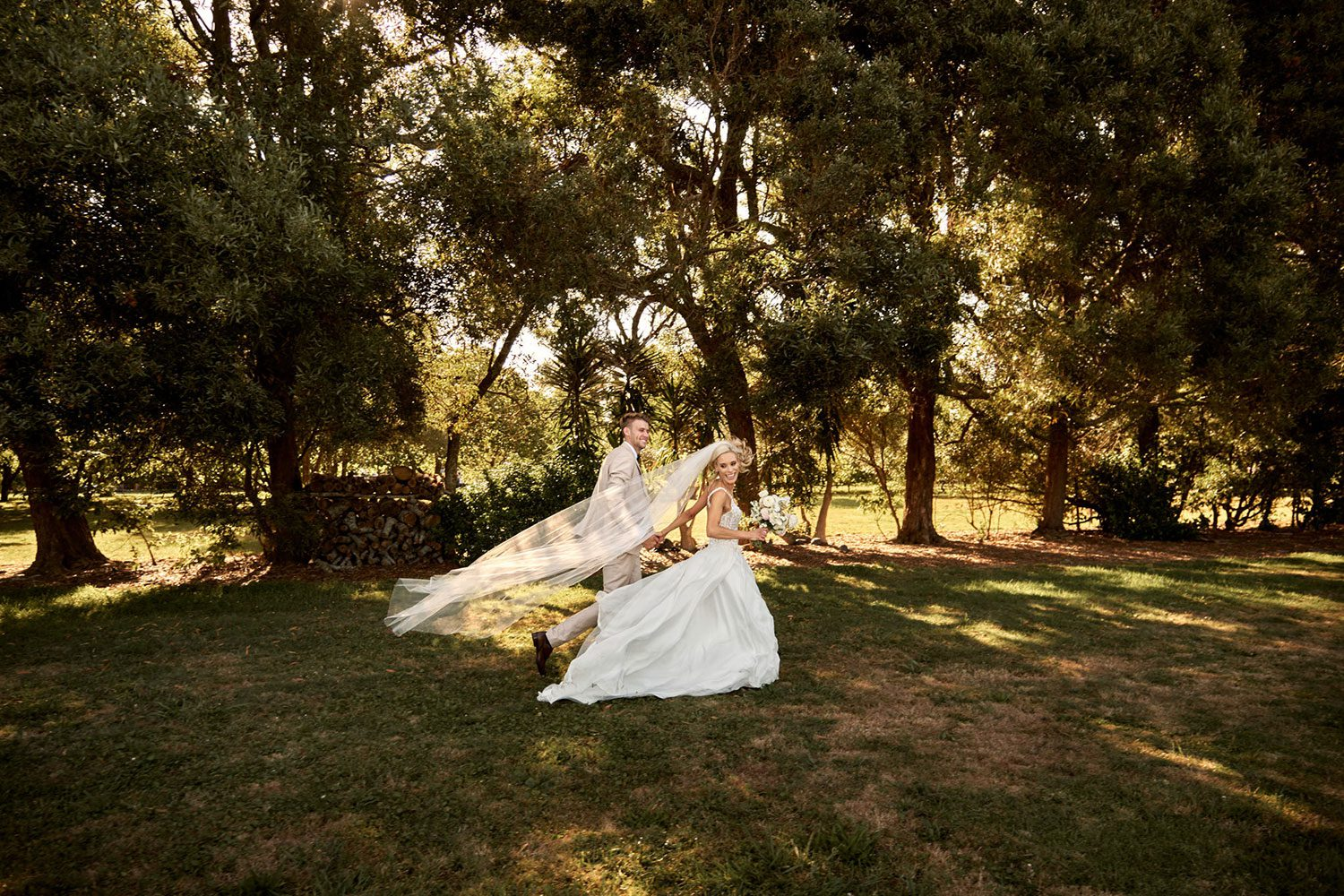 Bride wearing bespoke gown made of silk chiffon with delicate flower lace bodice by Vinka bridal designer Auckland - walking away with groom outside veil in wind