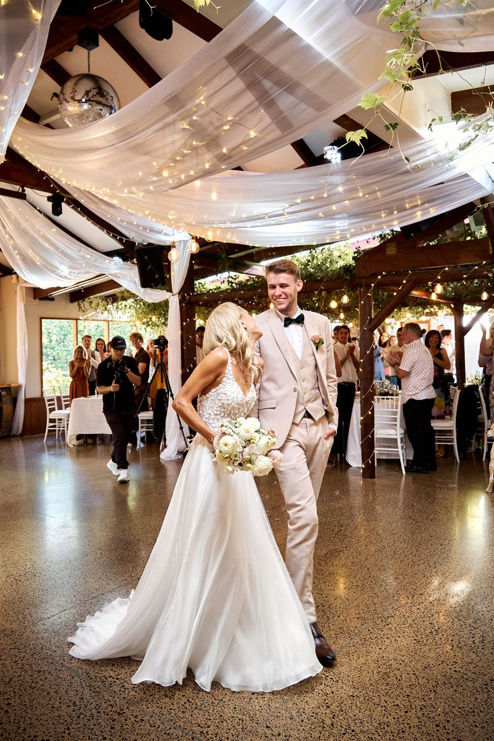 Bride wearing bespoke gown made of silk chiffon with delicate flower lace bodice by Vinka bridal designer Auckland - at reception with groom