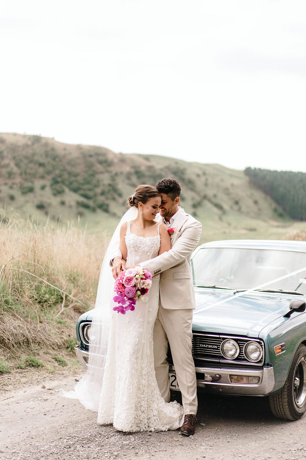 Bride wears bespoke E'More lace gown with boned bodice with hand beaded flower applique and full lace train by Auckland wedding dress maker Vinka designs - with groom in front of vintage car